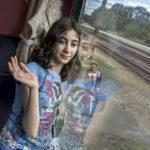 Ein afghanisches Flüchtlingsmädchen winkt kurz vor der ungewissen Fahrt vom Flüchtlingslager im ungarischen Bicske nach Deutschland.