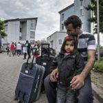 Vater und Tochter einer afghanischen Flüchtlingsfamilie sitzen erschöpft vor der Landesaufnahmestelle für Flüchtlinge (LASt) in Karlsruhe.