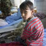 Der achtjährige Abdullah Amar sitzt am Krankenbett seines Vaters, der durch eine Sprengfalle verwundet wurde. Im Hintergrund Mayor Abdullah Stony.