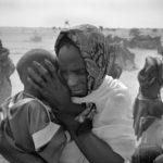 Eine Flüchtlingsfrau schützt ihr Kind vor dem aufkommenden Sandsturm.