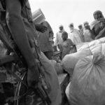 """Das """"Croix-Rouge du Tchad"""" bringt die Flüchtlinge in eine neues Flüchtlingscamp. Im Vorfeld des Abtransportes überprüft ein Soldat der Grenztruppen das Gepäck der Flüchtlinge."""