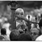 """Ein Flüchtlingskind aus der DDR klammert sich an die Eingangspforte zum Flüchtlingslager auf dem Gelände der Pfarrkirche zur """"Heiligen Familie"""" in Budapest-Zugliget. Im Sommer 1989 durchliefen bis zur Öffnung der Grenze am 10.09 ca. 40 000 DDR-Bürger drei in Ungarn eingerichtete Flüchtlingslager."""