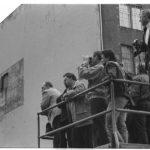 Während der Feierlichkeiten zum 40. Gründungstag der DDR haben sich auf West-Berliner Seite am Checkpoint Charlie Schaulustige versammelt, die den Aufmarsch der DDR-Grenzsoldaten am Grenzkontrollpunkt Checkpoint Charlie beobachten.