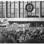 """Im Zuge landesweiten Montagsdemonstrationen gehen Ostberliner Studenten für mehr Selbstbestimmung auf die Straße. Im Hintergrund der """"Palast der Republik""""."""