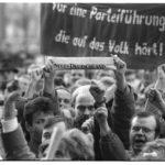 """9. November 1989, gegen 16:00 Uhr: während der außerordentlichen Mitgliederversammlung zur 10. ZK-Tagung versammeln sich Demonstranten vor dem Haus des Zentralkomitees der SED. Mit dem gefalteten """"Zentralorgan der Sozialistischen Einheitspartei Deutschlands"""" fordert ein Demonstrant ein """"Neues Deutschland""""."""