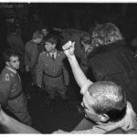 """Öffnung der Mauer am 9. November 1989: während schon viele der Grenzübergänge von zwischen Ost- und Westberlin geöffnet wurden, ist der Grenzübergang """"Friedrichstrasse"""" am Checkpoint Charlie immer noch geschlossen. Hinter dem Absperrtor stehen, wartend auf einen Befehl, unbeholfene Grenzbeamte."""