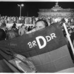 Öffnung der Mauer am 9. November 1989: Ost- und Westbürger Berlins feiern gemeinsam auf der Mauer vor dem Brandenburger Tor den Fall der Mauer. Ein Mann präsentiert die Wiedervereinigung in einer eigens angefertigten Flagge.