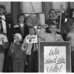 """Am Ende der Leipziger Wahlkundgebung mit Helmut Kohl auf dem Karl-Marx-Platz haben sich Kinder und Mitglieder eines Studentenkorps für ein Pressefoto aufgestellt. Kleiner Schönheitsfehler: der 2. Junge von rechts (untere Reihe) präsentiert den CDU-Slogan mit dem bewährten """"sozialistischen Gruß""""."""