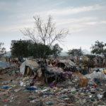 Das Slum der Waste-Picker bei Tagesanbruch. Rund 30 Familien leben hier in unmittelbarer Nähe der stinkenden und unter starker Rauchentwicklung schwelenden Müllkippe in Behausungen aus ausrangierten Wahlplakaten, Pappstücken und Lumpen.